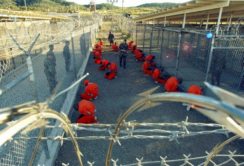 A file photo shows detainees sitting in a holding area watched by military police at Camp X-Ray inside Naval Base Guantanamo Bay